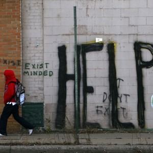 DETROIT - NOVEMBER 20: A pedestrian walks by graffiti on a downtown street November 20, 2008 in Detroit, Michigan. An estimated one in three Detroiters lives in poverty, making the city the poorest large city in America. The Big Three U.S. automakers, General Motors, Ford and Chrysler, are appearing this week in Washington to ask for federal funds to curb to decline of the American auto industry. Detroit, home to the big three, would be hardest hit if the government lets the auto makers fall into bankruptcy. (Photo by Spencer Platt/Getty Images)